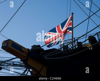 The Union Jack flies from the jack staff of HMS Victory. The worlds oldest commissioned warship. Red white blue - Stock Photo