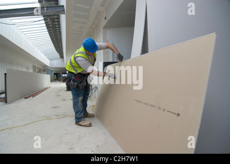 Cutting and measuring plasterboard - Stock Photo