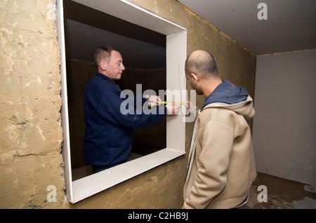 Fitting plasterboard around a window - Stock Photo