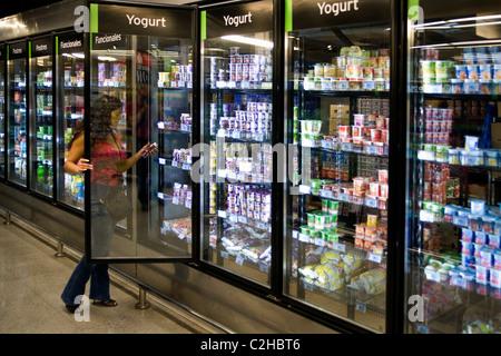 Woman picking yogurt from the fridge in a Supermarket - Stock Photo