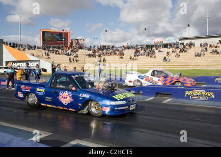 Two heavily modified and supercharged Australian Holden ute drag racing cars line up to race on the quarter mile - Stock Photo