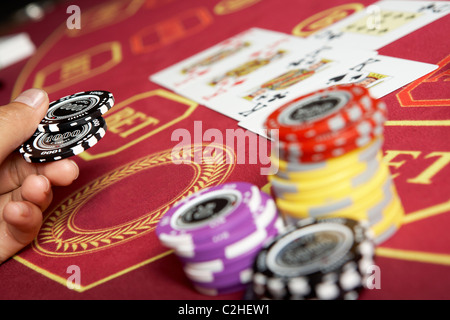 Image of black chips in hand over casino table - Stock Photo