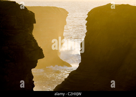 Sunset illuminates a chasm in the atlantic cliffs near Loop Head, County Clare, Ireland. - Stock Photo