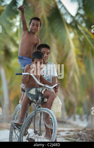 Three native island boys riding one bicycle down island coral, palm tree lined road. - Stock Photo