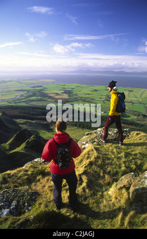 Walkers looking over Magilligan Point from the summit of Binevenagh, County Derry, Northern Ireland. - Stock Photo