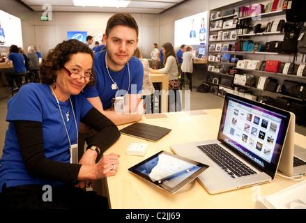 Friendly Apple store staff advisors in the Apple Store, the Grand Arcade, Cambridge UK - Stock Photo