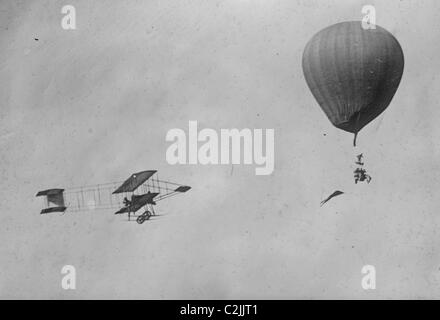 Paulhan in aeroplane greets his wife in a balloon, both in flight - Stock Photo
