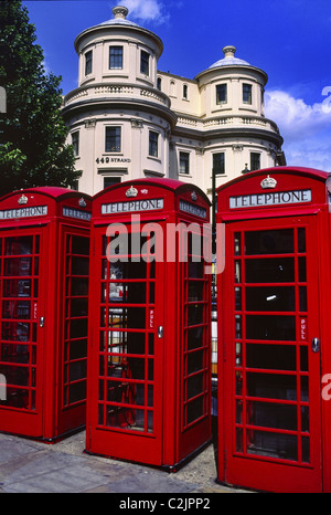 Colorful red telephone boxes in The Strand in sunny London England against a background of  J. Nash architecture - Stock Photo