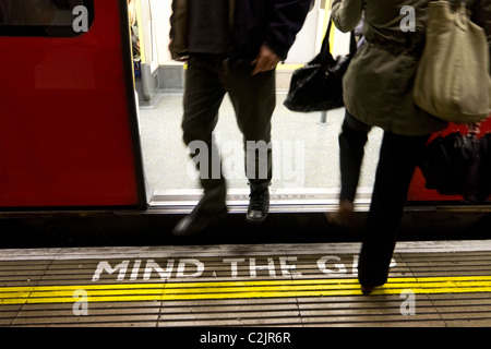 People exit and enter a London Underground tube train over a Mind the Gap warning, London, England - Stock Photo