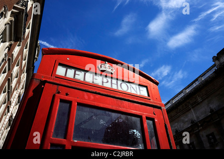 Low angle shot of a red telephone box and blue sky in London, England, UK - Stock Photo