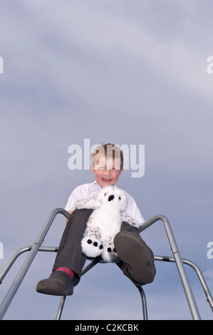 A MODEL RELEASED picture of a seven year old boy and his cuddly toy outdoors on a climbing frame in the Uk - Stock Photo