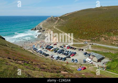 Chapel Porth car park and beach in Cornwall UK near high tide. - Stock Photo