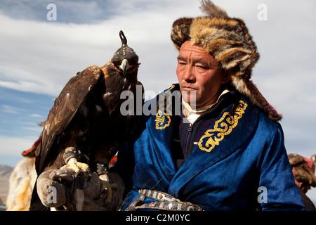 Mongolian Kazakh Eagle Hunter in traditional dress with hooded eagle,  at Eagle Festival, Western Region, Mongolia - Stock Photo