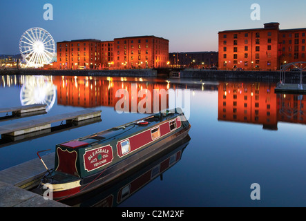 Narrowboat at Salthouse Dock, Liverpool at night with the buildings of the Albert Dock and the Echo Big Wheel in - Stock Photo
