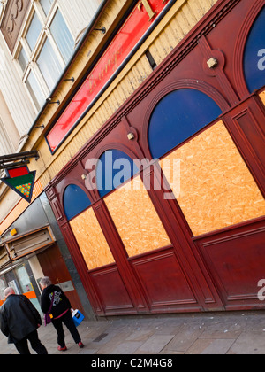 Pedestrians walking past boarded up pool hall in Nottingham City centre England UK - Stock Photo