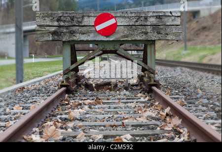 wooden buffer stop with red stop sign ending rail tracks concept for limit, limitation restriction boundary, prohibited, - Stock Photo