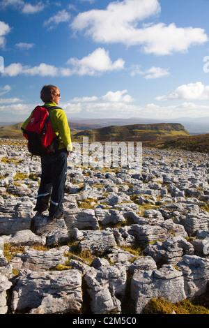 Walker amid  limestone pavement on Keelogyboy Mountain, County Leitrim, Ireland. - Stock Photo
