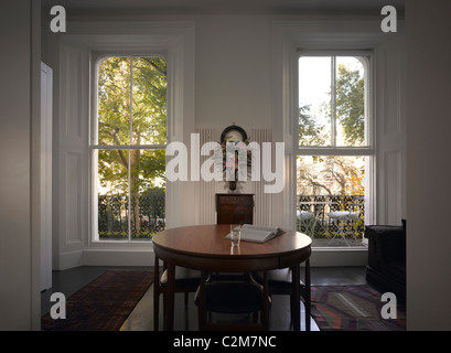 Le Cabinet, Notting Hill, London. Compact room with dining table and two traditional sash windows - Stock Photo