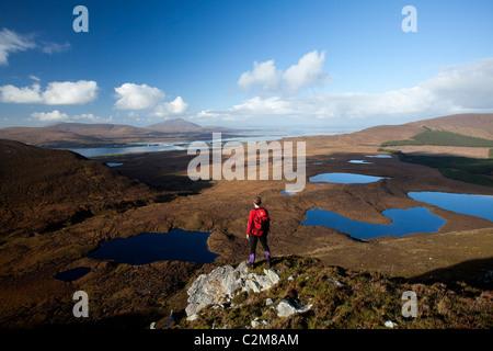 Walker looking towards Achill Island from Corraun Hill, County Mayo, Ireland. - Stock Photo