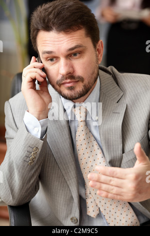 Portrait of a mature business man screaming in his cellphone in office environment - Stock Photo