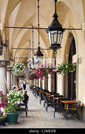 Colourful flowers and hanging baskets outside a cafe on a arched walkway outside the Cloth Hall or Sukiennice in - Stock Photo