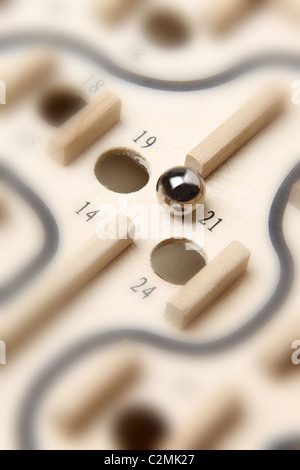 Chrome ball about to drop into a numbered hole of the wooden board game Shut the Box - Stock Photo