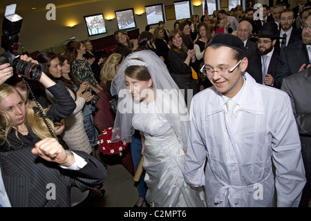 Newly weds enter the reception hall after being married in an Orthodox Jewish wedding ceremony in Brooklyn, New - Stock Photo