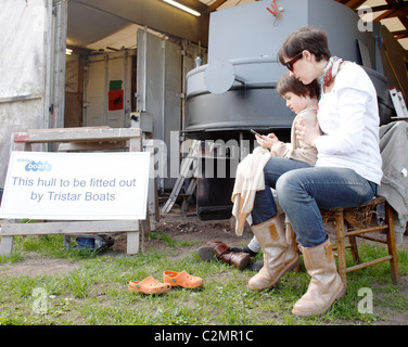 A young boy playing with his mum's mobile phone at a boat shed. - Stock Photo