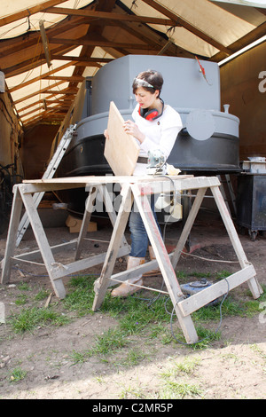 A woman standing at trestles, inspecting the sanding work of a wooden door, wearing Personal Protective Equipment - Stock Photo