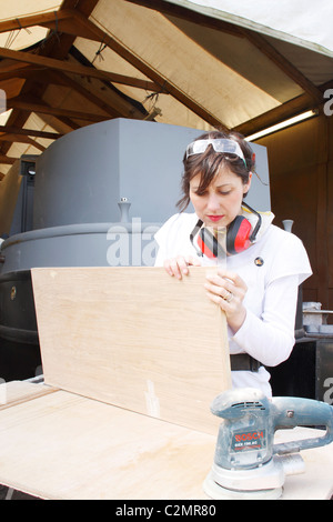 A woman inspecting the sanding work of a wooden door, wearing Personal Protective Equipment (PPE). - Stock Photo