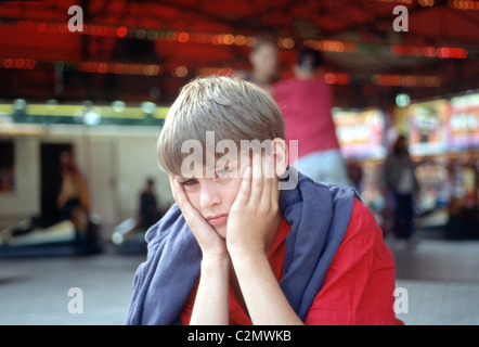 Depressed boy at fairground - Stock Photo