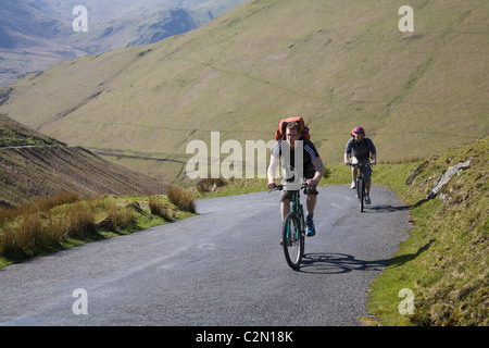 Lake District Cumbria England Two young men on mountain bikes reaching the summit of Newlands Pass - Stock Photo