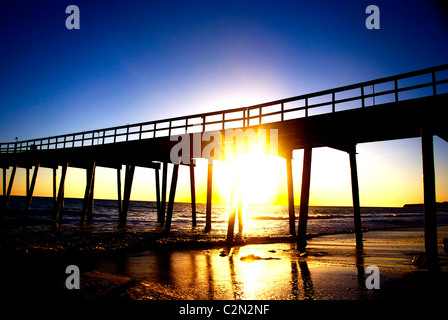 The Bright sun shining straight under a pier lighting up the photo - Stock Photo