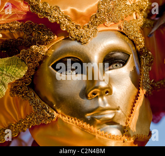 A woman wearing a golden mask during Venice carnival, Venice, Italy - Stock Photo