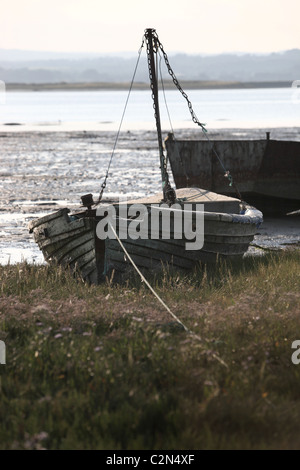 Old fishing boat moored up on bank - Stock Photo