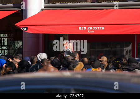 Dozens of Harlem residents outside the Red Rooster restaurant in Harlem, New York City waiting for President Obama - Stock Photo