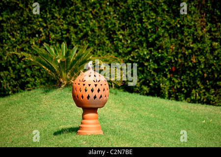 A small bird sitting on a terracota lamp in a garden, - Stock Photo
