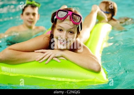 Photo of happy girl in pool with her friends on backround - Stock Photo