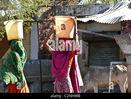 Pretty young village women carrying bucket full of fresh clean water drawn from well in rural village of Rajasthan - Stock Photo