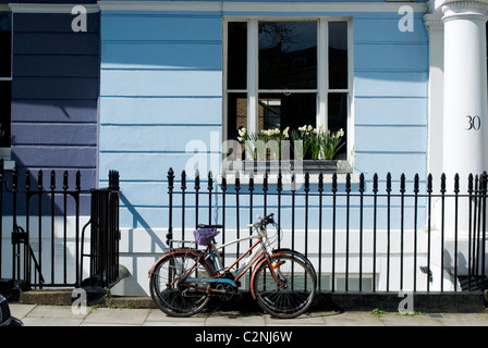 Bicycle parked in front of one of the colourful terrace houses of Chalcot Square, near Primrose Hill, London, NW1, - Stock Photo