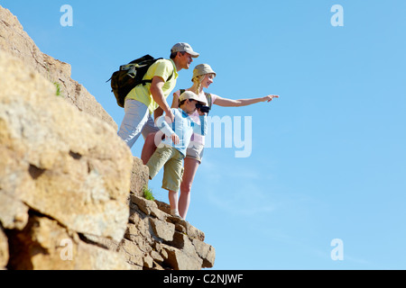 Portrait of family members looking afar outside while standing on cliff - Stock Photo