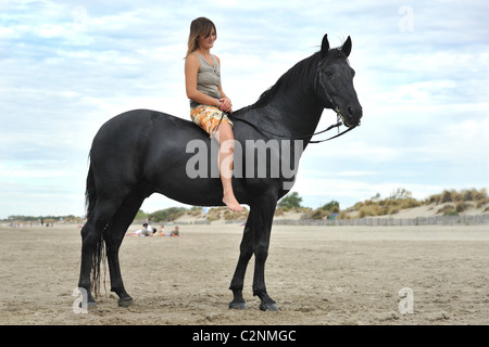 beautiful black horse on the beach and beautiful woman - Stock Photo