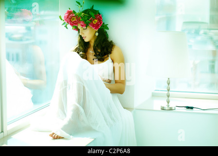 Beautiful woman in white dress sitting on window sill and looking through glass - Stock Photo