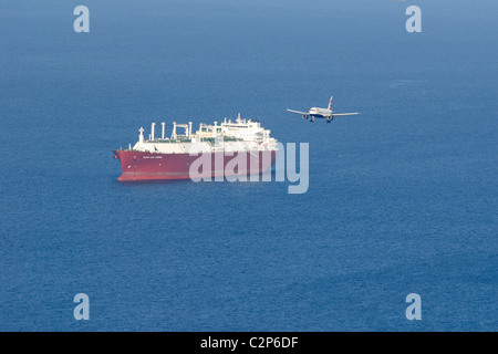 Monarch airways twin engined jet on approach to Gibraltar with large tanker at anchor in the waters off the coast - Stock Photo