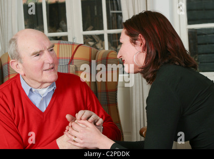 Woman looking after man older or voluntary worker - Stock Photo