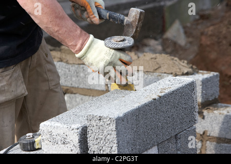 bricklayer using a hammer and brick chisel bolster to cut half cement breeze blocks building a block retaining wall - Stock Photo