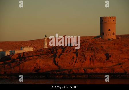Oman, Sur, view of watch tower on hill with buildings in the background against sky at dusk - Stock Photo