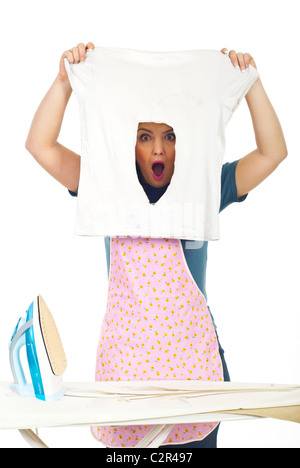 Shocked woman holding a burned iron shirt and looking through the hole made by the iron - Stock Photo
