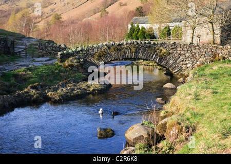 Quaint old packhorse bridge over Watendlath Beck in the Lake District National Park. Watendlath, Cumbria, England, - Stock Photo