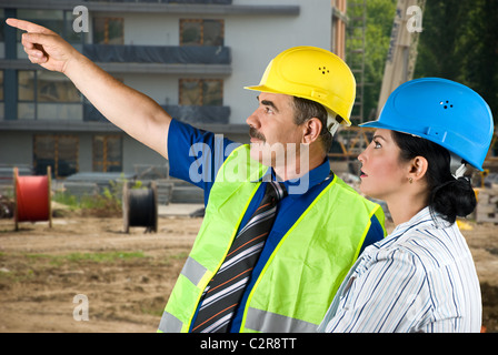 Two architects mature man and young woman working on site,the man pointing to somewhere and they have a discussion - Stock Photo